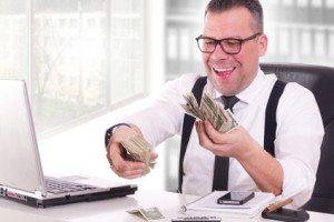 glücklicher Geschäftsmann beim Geld zählen